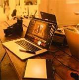 Es liegt ein Laptop und eine Kamera auf den Tisch